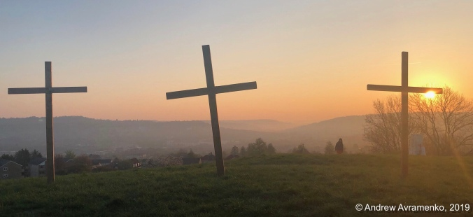 Sunrising behind 3 crosses on a hill