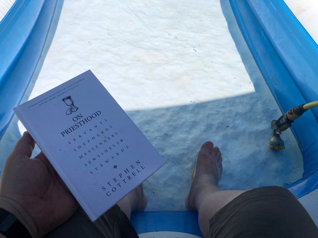 Feet in a paddling pool and a hand holding a book on the Priesthood.